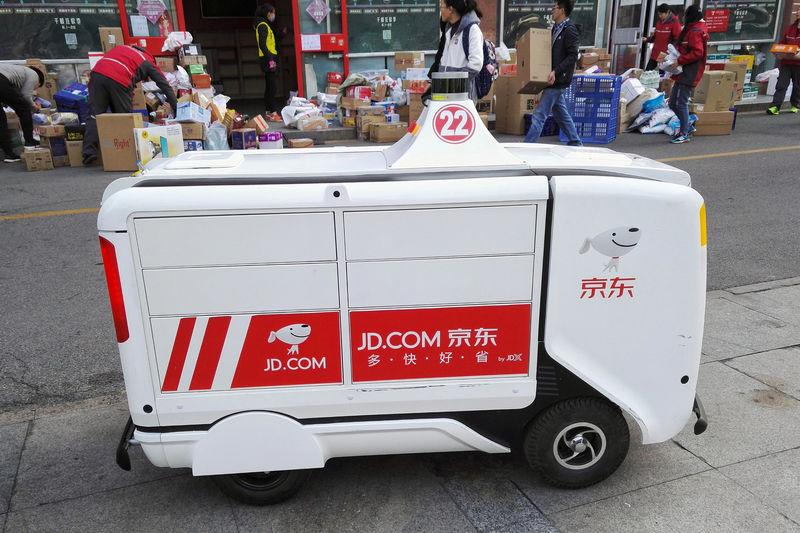 A JD.com driverless delivery robot is seen in front of parcels outside a JD.com logistics station at Renmin University of China a day after the Singles Day online shopping festival, in Beijing, China November 12, 2018. Liu Hongsheng/Qianlong.com via REUTERS
