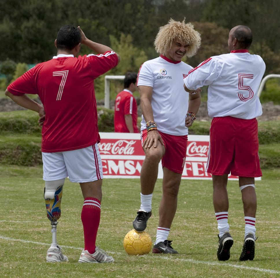 "Colombian former football star Carlos Valderrama (C) talks with his teammate Diego Leon Osorio (R) during a friendly match against the ""More sport-less mines"" team, composed by victims of landmines, in the framework of the WC2011 U-20 tournament, in Bogota, on July 27, 2011. AFP PHOTO/Luis Acosta (Photo credit should read LUIS ACOSTA/AFP/Getty Images)"