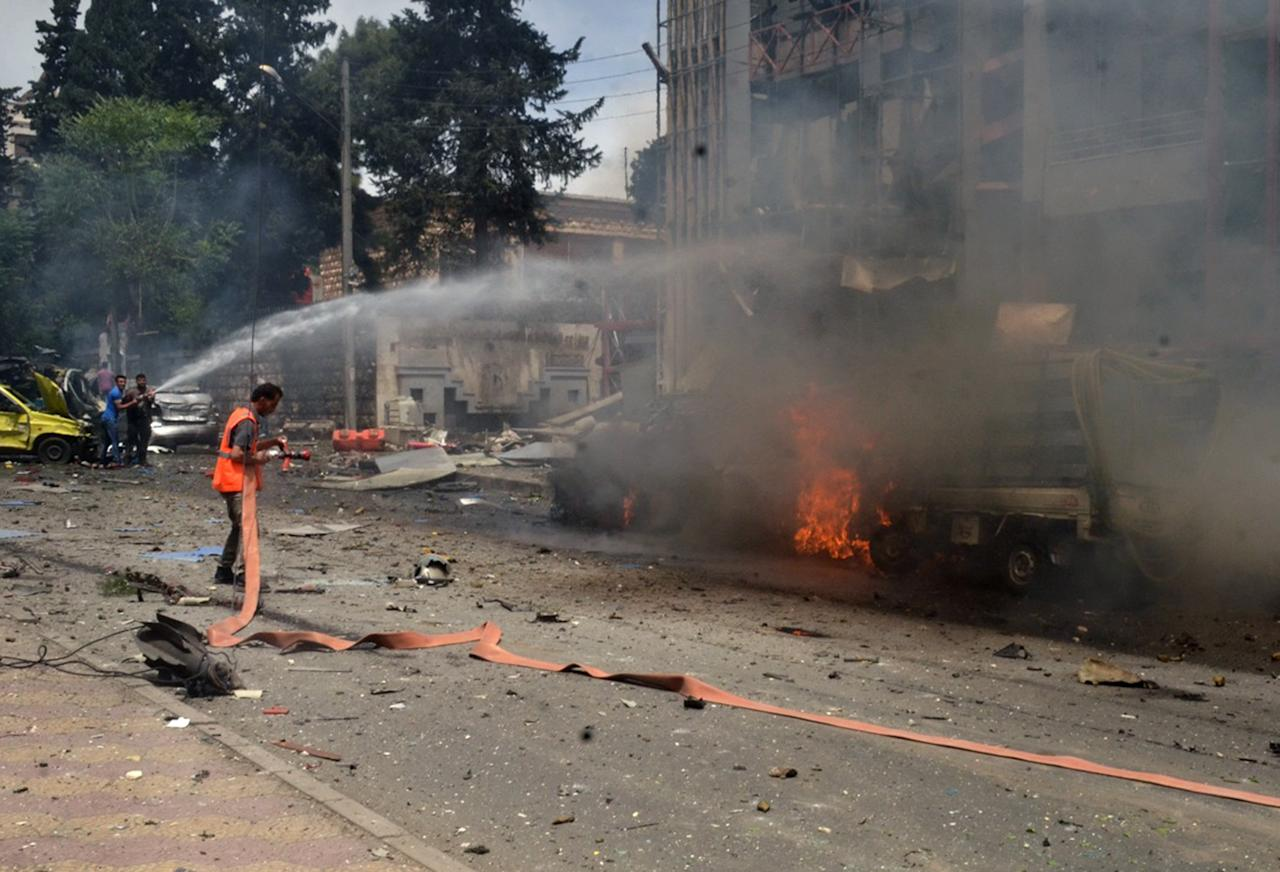 """In this photo released by the Syrian official news agency SANA, Syrian citizens and firefighters gather at the scene where one of rockets hit the Dubeet hospital in the central neighborhood of Muhafaza in Aleppo, Syria, Tuesday, May 3, 2016. Shells and mortar rounds are raining down on every neighborhood Aleppo,"""" said Aleppo-based health official Mohammad Hazouri, speaking from Al-Razi hospital. He said four people were killed and more than 30 wounded in Dubeet hospital alone, adding that half the casualties at the hospital were women and children. (SANA via AP)"""