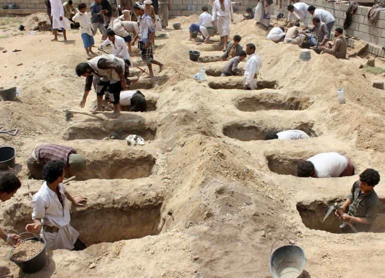 Yemenis dig graves on August 10, 2018, for children killed in an air strike on their bus in northern Yemen