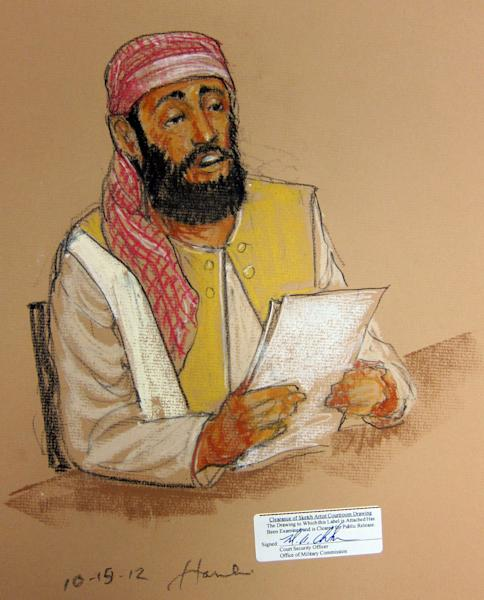 In this photo of a sketch by courtroom artist Janet Hamlin and reviewed by the U.S. Department of Defense, Ramzi Binalshibh, one of the five Guantanamo prisoners charged in the Sept. 11 attacks, sits at a defense table holding a document waiving his right to claim conflict of interest in representation, during the Military Commissions pretrial hearing in the Guantanamo Bay U.S. Naval Base in Cuba, Monday, Oct. 15, 2012. The five accused of the Sept. 11 attacks were back before a military tribunal, forgoing the protest that turned their last appearance into an unruly 13-hour spectacle. (AP Photo/Janet Hamlin, Pool)
