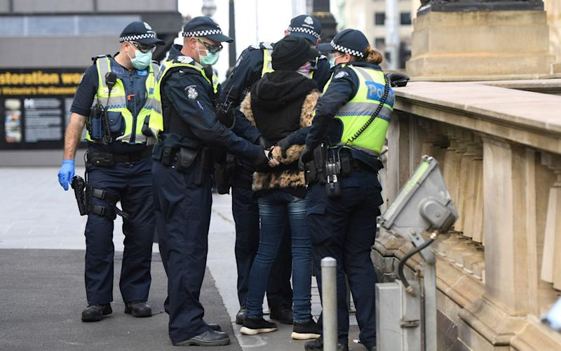 A woman is detained during an anti-lockdown protest in Melbourne - ERIK ANDERSON/EPA-EFE/Shutterstock