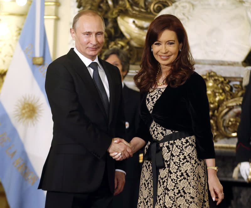 Argentina's President de Kirchner shakes hands with her Russian counterpart Putin in Buenos Aires
