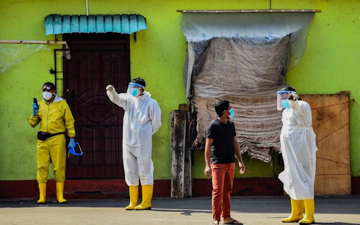 Health workers wearing protective gear wait to collect swab samples from residents to test for the Covid-19 coronavirus in Colombo - Ishara S. KODIKARA / AFP