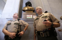 FILE - In this Aug. 14, 2017, file photo, Tennessee State Troopers stand near a bust of Confederate Gen. Nathan Bedford Forrest after protesters covered it and placed signs in front in Nashville, Tenn. Activists and Democratic lawmakers have called for the removal of a bust of Forrest from the state Capitol. (AP Photo/Mark Humphrey, File)