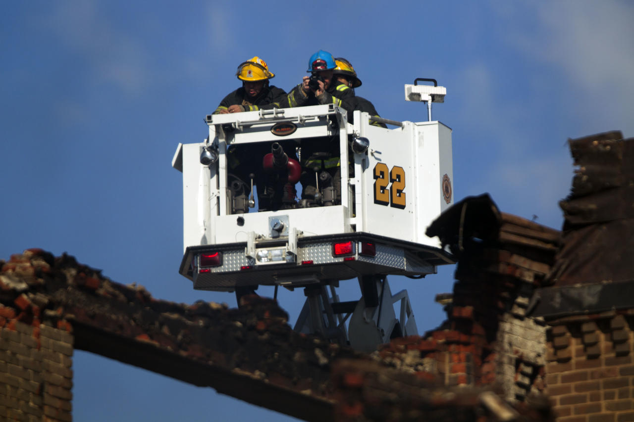 Firefighters inspect the aftermath of a fire in a warehouse on York Street near Kensington Avenue in Philadelphia on Monday, April 9, 2012. Two firefighters died after a wall collapsed on them while they fought the massive early-morning blaze. (AP Photo/Matt Rourke)