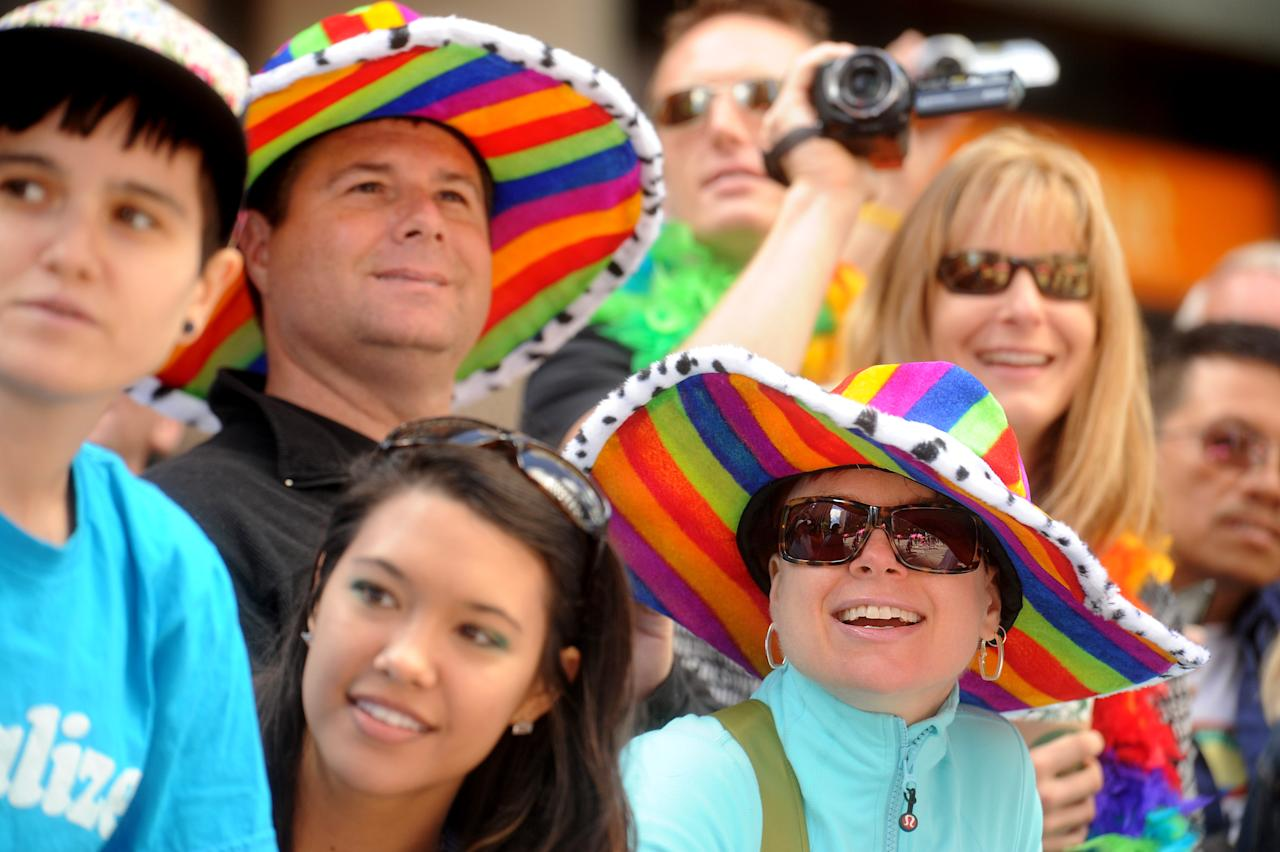 Lisa MacKenzie and Shane Cluff don rainbow hats as they watch San Francisco's 42nd annual Gay Pride parade on Sunday, June 24, 2012. (AP Photo/Noah Berger)