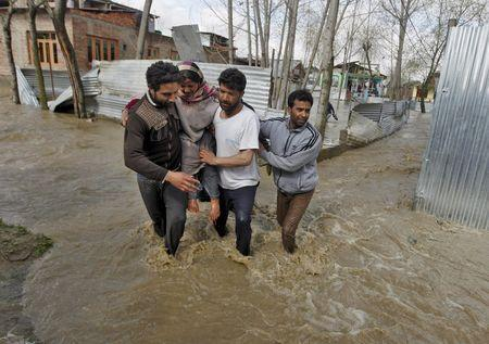 A woman is carried to a safer place from her partially submerged house after incessant rains in Srinagar March 30, 2015. REUTERS/Danish Ismail