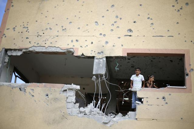 Palestinians look out of their house, which witnesses said was damaged during the Israeli offensive, on the fourth day of a five-day ceasefire in Johr El-Deek village near the central Gaza Strip August 17, 2014. Prime Minister Benjamin Netanyahu said on Sunday any deal on Gaza's future at truce talks in Cairo must be contingent on Israel's security needs, cautioning Hamas against carrying out its threat of a long war if Palestinian demands are not met. With a five-day ceasefire due to expire late on Monday, negotiators were to reconvene in the Egyptian capital to seek an end to five weeks of hostilities that have killed more than 2,000 people. REUTERS/Ibraheem Abu Mustafa (GAZA - Tags: POLITICS CIVIL UNREST)