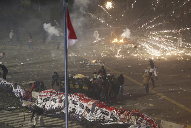 Supporters of the losing presidential candidate take cover with police shields as fireworks explode during clashes with police Wednesday, May 22, 2019, in Jakarta, Indonesia. Indonesian President Joko Widodo said authorities have the volatile situation in the country's capital under control after a number of people died Wednesday in riots by supporters of his losing rival in last month's presidential election. (AP Photo/Achmad Ibrahim)
