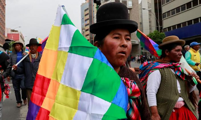 """<span class=""""element-image__caption"""">A supporter of the former Bolivian president Evo Morales holding a Wiphala flag takes part in a protest, in La Paz, Bolivia, on Thursday.</span> <span class=""""element-image__credit"""">Photograph: Henry Romero/Reuters</span>"""