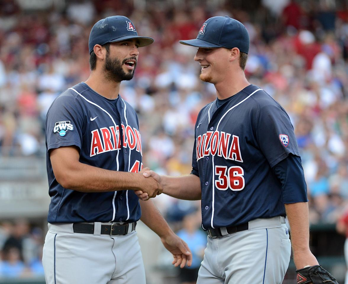 OMAHA, NE - JUNE 25:  James Farris #36 of the Arizona Wildcats reacts with Michael Lopez #45 to after an out to end the third inning against the South Carolina Gamecocks during game 2 of the College World Series at TD Ameritrade Field on June 25, 2012 in Omaha, Nebraska.  (Photo by Harry How/Getty Images)