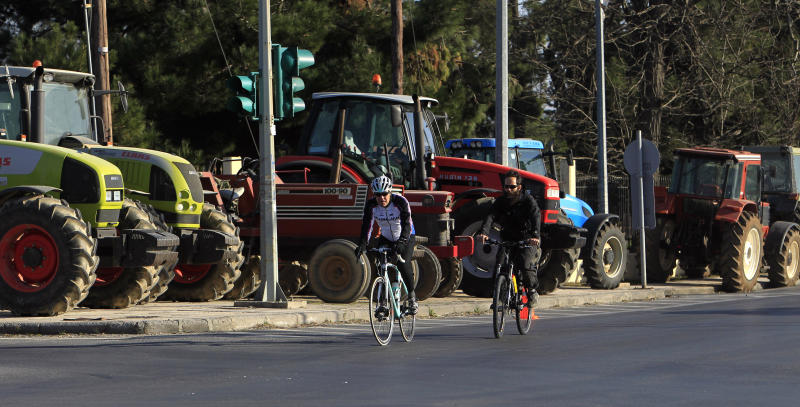 Cyclists pass in front of parked tractors during a protest in the northern Greek port city of Thessaloniki, Tuesday, Feb. 5, 2013. Farmers are threatening to block highways across the country to protest new tax laws, spending cuts and high fuel taxes. (AP Photo/Nikolas Giakoumidis)