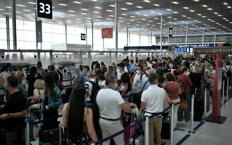 Travelelrs, wearing protective face masks, line up at a check-in desk of the Orly Airport, south of Paris on August 1, 2020 during a major weekend of the French summer holidays - Stephanie de Sakutin/AFP
