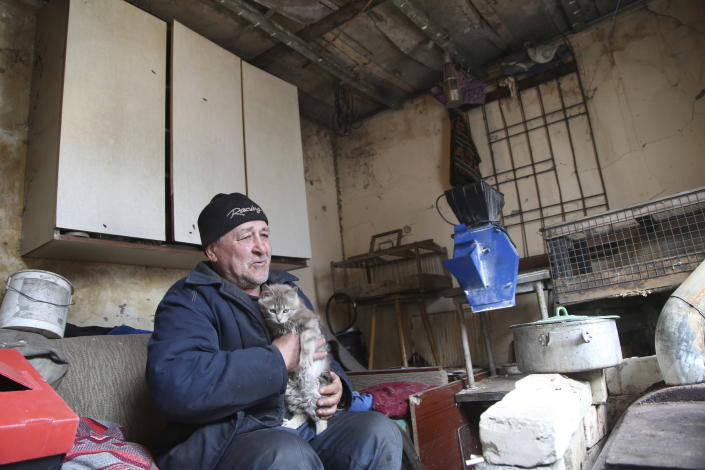 A man visits his home in the separatist-controlled territory to collect his cat after a recent shelling near a frontline outside Donetsk, eastern Ukraine, Friday, April 9, 2021. Tensions have built up in recent weeks in the area of the separatist conflict in eastern Ukraine, with violations of a cease-fire becoming increasingly frequent. (AP Photo)