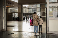A woman and a child stand at the main entrance of the school Athenee Leonie de Waha in Liege, Belgium, Tuesday, Jan. 12, 2021. Fed up with the COVID-19 restrictions keeping them at home most of the time, students in the last two years of high school in the city of Liege launched an online petition asking for more in-person class time. The students' efforts paid off Tuesday following an online meeting with Mayor Willy Demeyer and education officials in the city. The officials pledged to revisit the current COVID-19 protocol in a bid to get the 16 to 18-year-olds in-person instruction at least half-time starting Monday. (AP Photo/Valentin Bianchi)