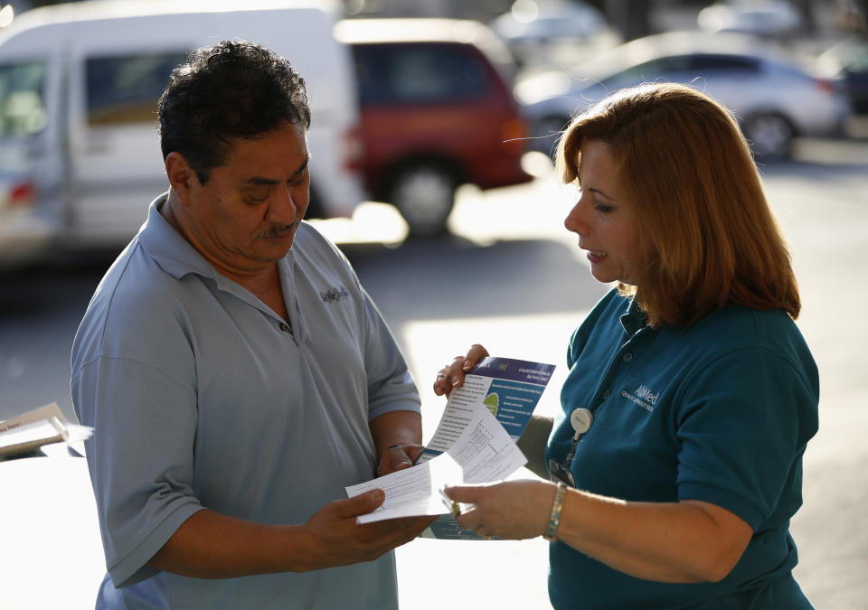 Engrith Acosta, patient care coordinator at AltaMed, speaks to a man during a community outreach on Obamacare in Los Angeles, California November 6, 2013. Concerns among Hispanics that signing up for medical insurance under President Barack Obama's healthcare law may draw the scrutiny of immigration authorities has hurt enrollment, according to advocates of the policy. To match Feature USA-HEALTHCARE/HISPANICS  Picture taken November 6, 2013. REUTERS/Mario Anzuoni  (UNITED STATES - Tags: POLITICS HEALTH)