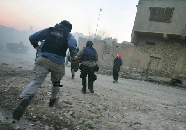 <p>Journalists, U.S. troops and Iraqi police run for cover during a firefight with insurgents January 16, 2005 in Tal Afar, Iraq. A routine patrol in the insurgent stronghold turned into an hour-long running gunbattle January 16, with a combined U.S. and Iraqi police force battling insurgents across alleys and down boulevards. Despite several close calls, there were no U.S. or Iraqi police casualties. (Photo by Chris Hondros/Getty Images) </p>