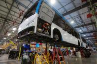 Workers build electric buses at the BYD electric bus factory in Lancaster, California
