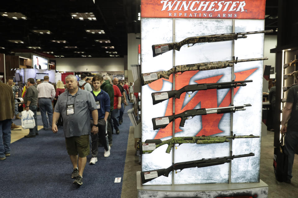 Gun enthusiasts walk through the gun displays in the exhibition hall at the National Rifle Association Annual Meeting in Indianapolis, Saturday, April 27, 2019. (AP Photo/Michael Conroy)