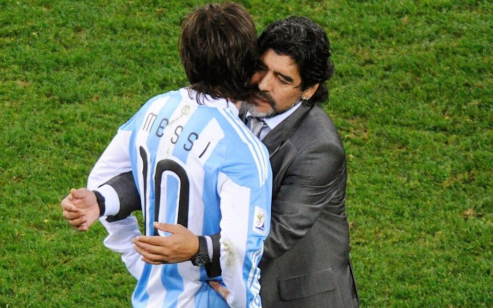 Argentinian national soccer team head coach Diego Maradona (R) embraces Lionel Messi (L) after the FIFA World Cup 2010  - Shutterstock