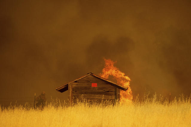 <p>Flames rise above outbuilding as the County fire burns in Guinda, Calif., July 1, 2018.(Photo: Noah Berger/AP) </p>