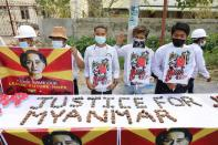 People hold a banner showing the portrait of Aung San Suu Kyi, in Mandalay