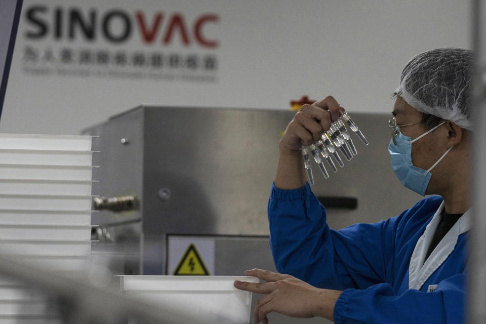 A worker inspects syringes of a vaccine for COVID-19 produced by Sinovac at its factory in Beijing on Thursday, Sept. 24, 2020. With rich countries snapping up supplies of COVID-19 vaccines, some parts of the world may have to rely on Chinese-developed shots to conquer the outbreak. The question: Will they work? (AP Photo/Ng Han Guan)