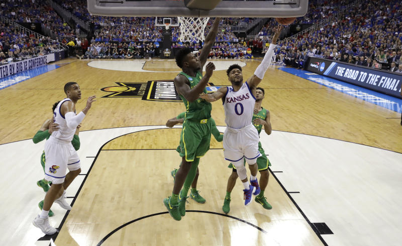 Kansas guard Frank Mason III (0) drives to the basket past Oregon forward Jordan Bell during the first half of a regional final of the NCAA men's college basketball tournament, Saturday, March 25, 2017, in Kansas City, Mo. (AP Photo/Charlie Riedel)