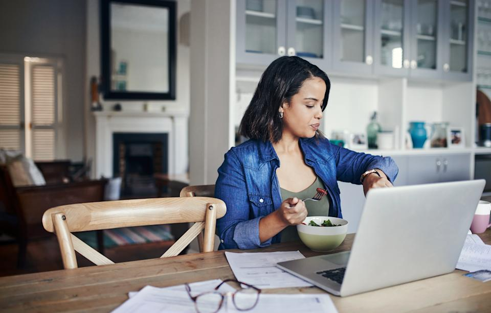 Shot of a young woman checking her watch and having a salad while working from home