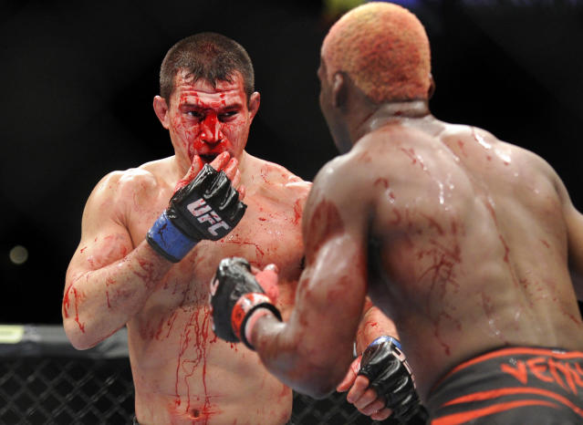 Bobby Voelker, left, wipes his face during his UFC 168 mixed martial arts welterweight bout against William Macario on Saturday, Dec. 28, 2013, in Las Vegas. Macario won by unanimous decision. (AP Photo/David Becker)