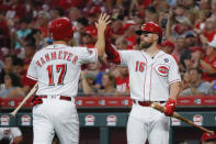 Cincinnati Reds' Josh VanMeter (17) celebrates with Tucker Barnhart (16) after scoring on an RBI-double by Scooter Gennett off Pittsburgh Pirates starting pitcher Alex McRae in the second inning of a baseball game, Monday, July 29, 2019, in Cincinnati. (AP Photo/John Minchillo)