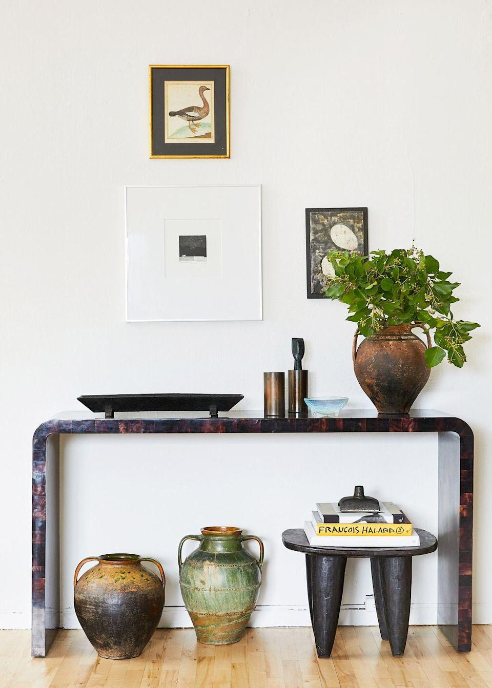 <p>When you don't have a double-tiered console table, you can still create a space for extra books and decorative objects. Get creative and use an accent stool when it's not being used as a seat. </p>