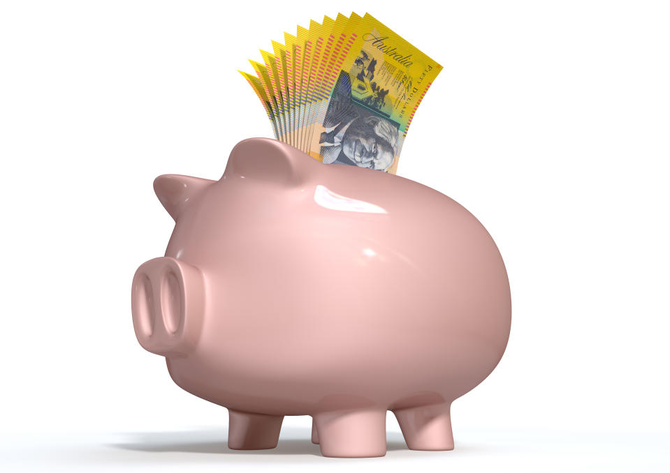 A pink ceramic piggy bank on an isolated white background with a wad of australian dollar notes stuffed into its slot