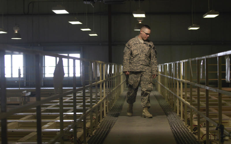 FILE – In this March 23, 2011, file photo a U.S. military guard watches over detainee cells inside the Parwan detention facility near Bagram Air Field in Afghanistan. Saturday, March 23, 2013, the Pentagon said the U.S. has reached an agreement with the Afghanistan government to transfer the facility to Afghan control. Defense Secretary Chuck Hagel spoke with Afghan President Hamid Karzai Saturday as officials finalized the agreement after days of intense negotiations. (AP Photo/Dar Yasin)