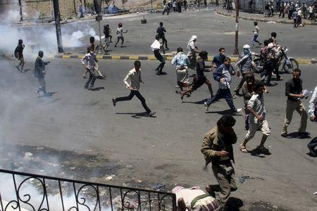 Anti-Houthi protesters seek refuge as pro-Houthi police troopers use tear gas to disperse them in Yemen's southwestern city of Taiz March 25, 2015. REUTERS/Anees Mahyoub