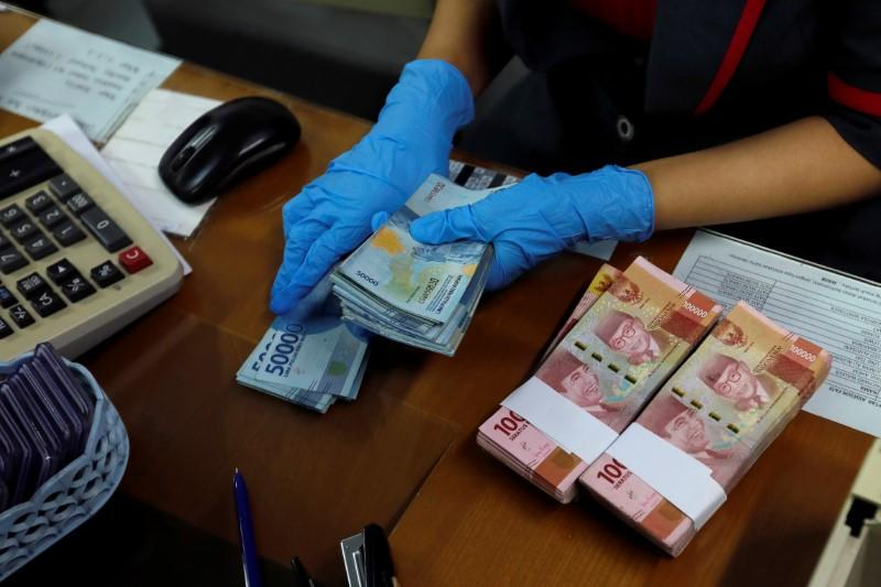 An employee wearing a face mask and synthetic gloves counts Indonesia's rupiah banknotes at a currency exchange office amid the spread of coronavirus disease (COVID-19) in Jakarta