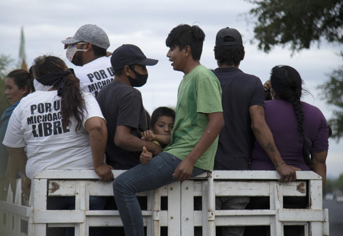"""People who say they are members of a female-led, self-defense group, some wearing T-shirts with a message that reads in Spanish: """"For a free Michoacan,"""" board the back of a truck at the end of their work shift at a checkpoint to protect the entrance of El Terrero in Michoacan state, Mexico, Thursday, Jan. 14, 2021. Some of the four dozen women warriors are pregnant; some carry their small children to the barricades with them. (AP Photo/Armando Solis)"""