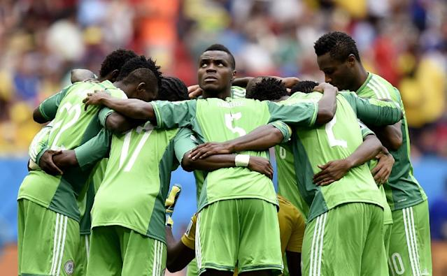 Nigeria's Emmanuel Emenike, center, looks up as his team form a huddle before the start of the second half during the World Cup round of 16 soccer match between France and Nigeria at the Estadio Nacional in Brasilia, Brazil, Monday, June 30, 2014. (AP Photo/Martin Meissner)