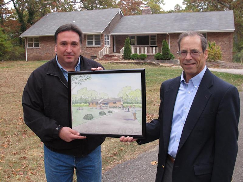 "In this Wednesday, Oct. 23, 2013 photo, Steve Fulgoni, left, and Ron Stein, two of the organizers of an effort to restore a home of jazz legend John Coltrane, hold an artist's rendering of the the Dix Hills, N.Y. site after restoration. This is where the saxophonist composed the epic 1964 jazz masterpiece ""A Love Supreme."" (AP Photo/Frank Eltman)"