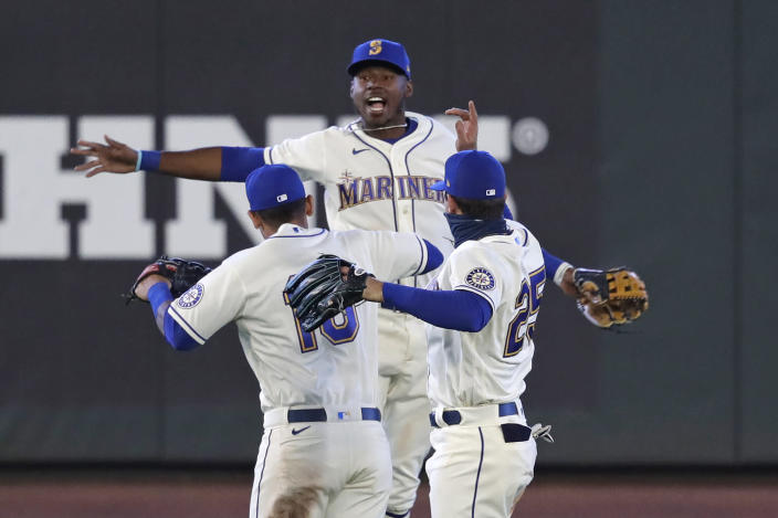 Seattle Mariners outfielders Kyle Lewis, center, Tim Lopes (10) and Dylan Moore (25) leap together in celebration after the team beat the Colorado Rockies in a baseball game Sunday, Aug. 9, 2020, in Seattle. (AP Photo/Elaine Thompson)