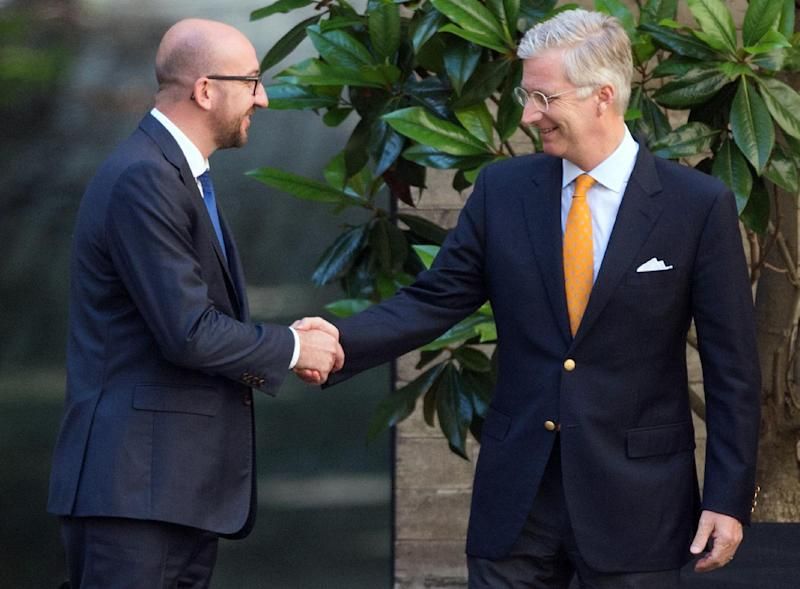 Charles Michel (L) shakes hands with King Philippe of Belgium after an audience at the Royal Palace in Brussels, Belgium, on July 14, 2014 (AFP Photo/Benoit Doppagne)