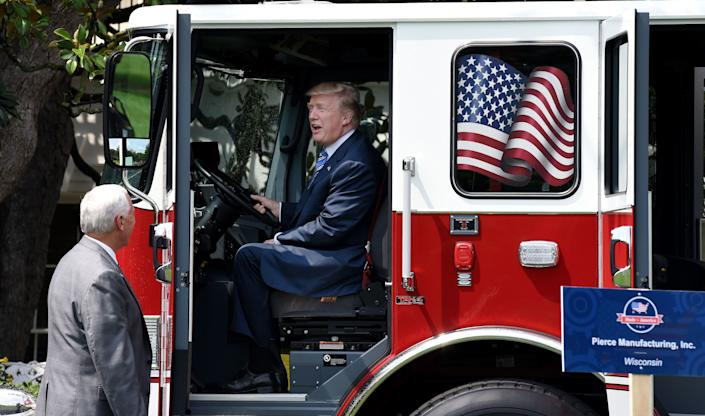 "President Donald Trump seems to like the view from a firetruck made by Wisconsin-based Pierce Manufacturing as Vice President Mike Pence stands by during ""Made in America"" week."