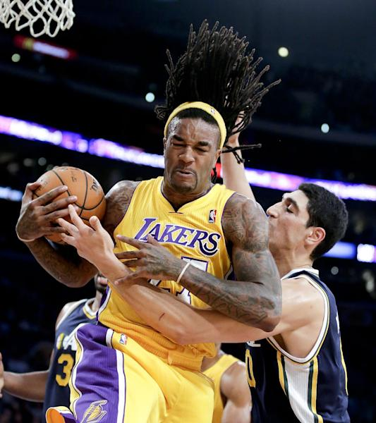 Los Angeles Lakers center Jordan Hill, left, fights over a rebound with Utah Jazz center Enes Kanter during the first half of a preseason NBA basketball game in Los Angeles, Tuesday, Oct. 22, 2013. (AP Photo/Chris Carlson)