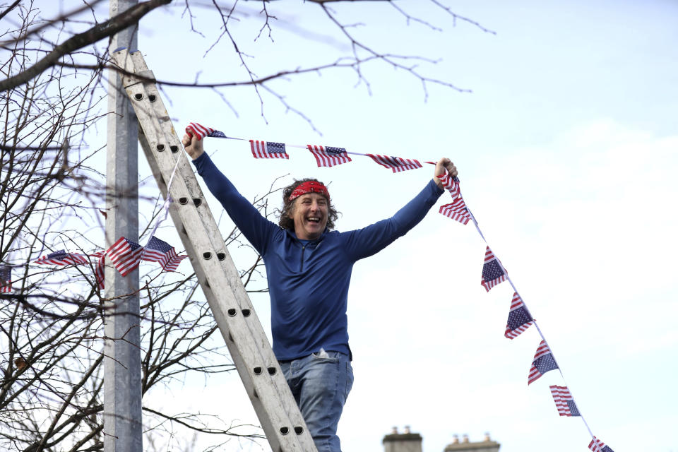 A man puts bunting up in the town of Ballina, the ancestral home of Joe Biden, in North West of Ireland, Saturday, Nov. 7, 2020. Biden was elected Saturday as the 46th president of the United States, defeating President Donald Trump in an election that played out against the backdrop of a pandemic, its economic fallout and a national reckoning on racism. (AP Photo/Peter Morrison)