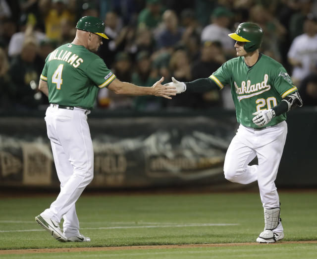 Oakland Athletics' Mark Canha, right, is congratulated by third base coach Matt Williams after hitting a home run off Houston Astros' Justin Verlander during the fifth inning of a baseball game Friday, Aug. 16, 2019, in Oakland, Calif. (AP Photo/Ben Margot)