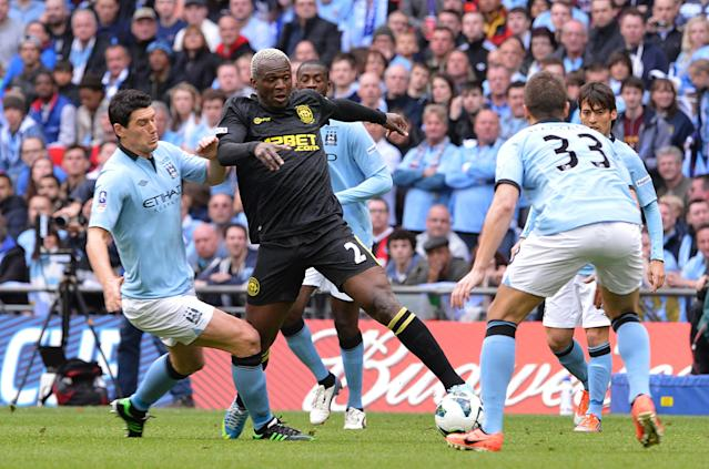 Wigan Athletic's Arouna Kone (centre) and Manchester City's Gareth Barry battle for the ball