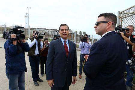 Attorney General of California Xavier Becerra walks along the U.S.-Mexico border at the Pacific Ocean after announcing a lawsuit against the Trump Administration over its plans to begin construction of border wall in San Diego and Imperial Counties, in San Diego, California, U.S., September 20, 2017. REUTERS/Mike Blake