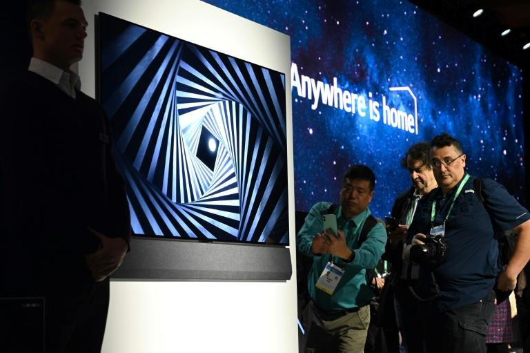Attendees view the super thin LG GX series OLED 8K television at a press conference at CES in Las Vegas on January 6