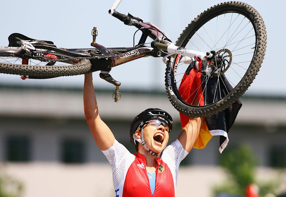 BEIJING - AUGUST 23: Sabine Spitz of Germany celebrates her victory in the Women's Cross Country mountain bike cycling event held at the Laoshan Mountain Bike Course on Day 15 of the Beijing 2008 Olympic Games on August 23, 2008 in Beijing, China. (Photo by Paul Gilham/Getty Images)